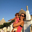 Mother and Daughter - Tourists in Alberobello with Trulli Houses - Stock Photo