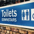 Toilets sign, blue on white background — Stock Photo