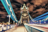 Tower Bridge in London, UK at night with traffic and moving red — Stock Photo