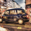Stock Photo: Motion blur picture of Black Cab at major road intersection in L