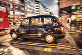 Motion blur picture of Black Cab at major road intersection in L — Stock Photo