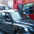 Stock Photo: Motion blur picture of Black Cab and Red Double Decker Bus in th