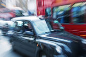 Motion blur picture of Black Cab and Red Double Decker Bus in th — Stock Photo