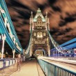 Stock Photo: Detail of Tower Bridge in London at night with car light trail -