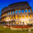Beautiful view of Colosseum at sunset with flowerbed in foreground — Stock Photo