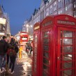 Royalty-Free Stock Photo: Red Telephone Booth in London on a crowded street at night