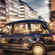 Motion blur picture of Black Cab at major road intersection — Stock Photo