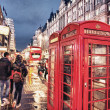 Red Telephone Booth in London on a crowded street at night - Stock Photo