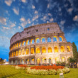 Colosseum - Rome. Night view with surrounding grass and park - Stock Photo