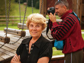 Senior Woman at the Park with photographer on background — Stock Photo