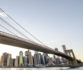 Upward view of Brooklyn Bridge at Sunset with Manhattan Skyline — Stock Photo