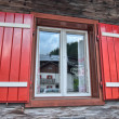 Typical red window of a wooden house, dolomites mountains — Stock Photo