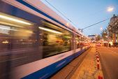 Amsterdam. Tram speeding at sunset in city streets — Stock Photo