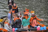 Amsterdam canals full of boats and in orange during the celebration of queensday — Stock Photo