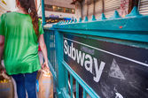 Girl passing in front of a Subway entrance in New York City — Stock Photo