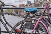 Amsterdam, Netherlands. Colourful bike over a bridge and city channels. — Stock Photo