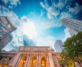 New York Public Library exterior with trees and surrounding buildings — Stock Photo