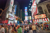 NEW YORK CITY - AUG 25: Tourists walk in the city lights of Time — Stock Photo