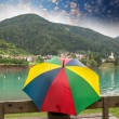 Woman watching mountain lake under a colourful umbrella — Stock Photo