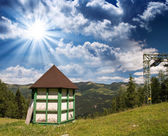 Hut on a mountain landscape with beautiful summer sky — Stock Photo