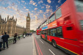 Iconic red bus passing over Westminster Bridge in London — Stock Photo