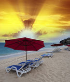 Desert beach with umbrellas and deckchairs at sunset — Stock Photo