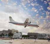 Airplane landing just above the beach at sunset — Stock Photo