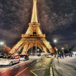 PARIS - NOV 30: Tourists walk underneath Eiffel Tower at dusk, N — Stockfoto