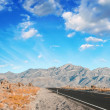 Long desert road in a mountain landscape — Stock Photo