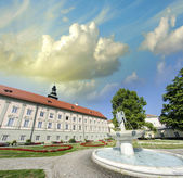 Ancient building in a beautiful city square with fountain and tr — Stock Photo
