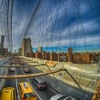 Taxi cab crossing the Brooklyn Bridge in New York, City skyline — Stock Photo