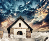 Small Church on a snowy Mountain Peak. Beautiful winter sunset c — Stok fotoğraf