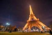 PARIS - NOV 30: Tourists walk underneath Eiffel Tower at dusk, N — Stock Photo