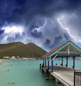 Thunderstorm over beautiful beach with jetty over water — Стоковое фото