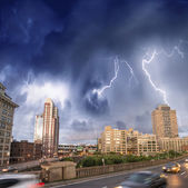 Escaping from city severe weather. Cars speeding up with lightni — Stock Photo