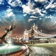 Stock Photo: Tower Bridge at Night, London. Girl with a Dolphin Fountain