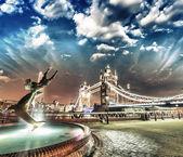 Mostu tower bridge nocą, londyn. dziewczyna z fontanna z delfinem — Zdjęcie stockowe