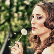 Stock Photo: Beautiful young womblowing on Taraxacum Flower