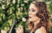 Beautiful young woman blowing on a Taraxacum Flower — Stock Photo