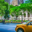 Stock Photo: Yellow cabs speeding up in front of New York Public Library