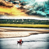 Man on his Canoe at sunset — Stock Photo