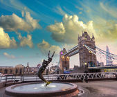 Girl and Dolphin statue against Tower bridge — Stock Photo