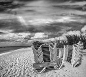 Deck chairs stacked on a beautiful beach — Stock Photo