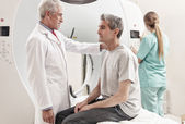 Senior male doctor explaining CT scanner exam to man in 40s. Fem — Stock Photo