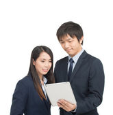 Asian businessman and businesswoman using tablet computer analyz — Photo