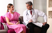 Happy male doctor speaking to woman patient about her health con — Stock Photo