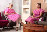 Two mature women patient talking in the hospital waiting room — ストック写真