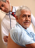 Male doctor examining elder patient at the hospital — Stock fotografie