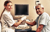 Woman doctor examing patient man wrist with ultrasound — Stock Photo