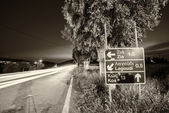 Road directions in Kos with car light trails — Stock Photo